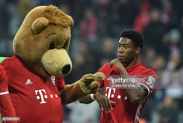 Bayern Munich's Austrian defender David Alaba interacts with the Bayern Munich mascot the German first division Bundesliga football match between FC...