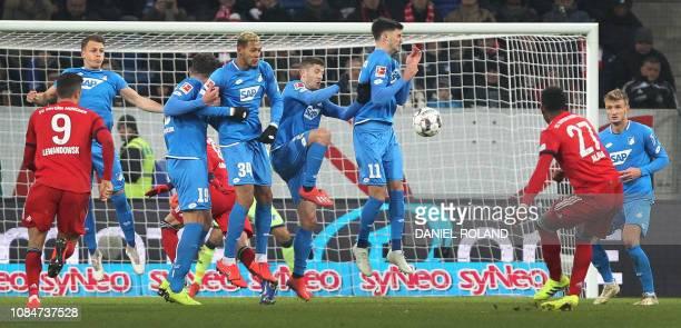 Bayern Munich's Austrian defender David Alaba shoots a free kick towards the Hoffenheim wall during the German First division Bundesliga football...