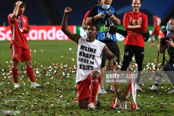 TOPSHOT Bayern Munich's Austrian defender David Alaba wearing a jersey reading in German My Strength Lies in Jesus poses with the trophy after Bayern...