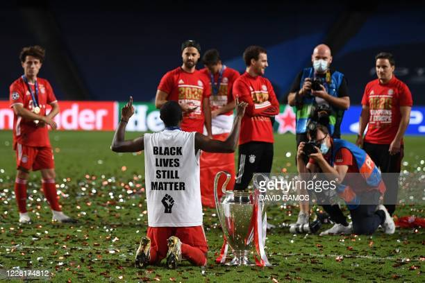 Bayern Munich's Austrian defender David Alaba wearing a jersey reading Black Lives Still Matter poses with the trophy after Bayern won the UEFA...