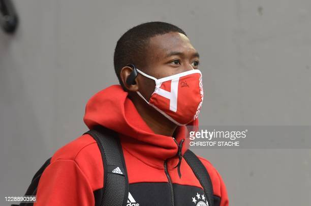 Bayern Munich's Austrian defender David Alaba wears a protective mask as he arrives to the German first division Bundesliga football match FC Bayern...