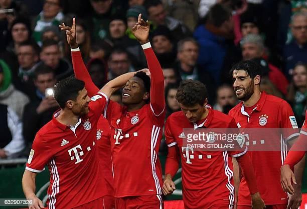 Bayern Munich's Austrian midfielder David Alaba and his teammates celebrate after scoring during the German first division Bundesliga football match...
