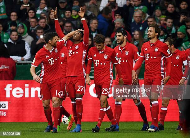 Bayern Munich's Austrian midfielder David Alaba and his teammates celebrate after scoring during the German first division Bundesliga football match...