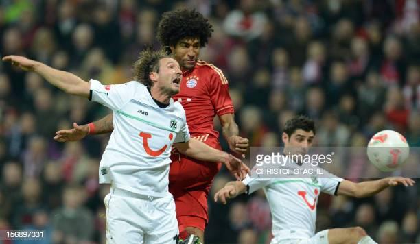 Bayern Munich's Brazil defender Dante heads the fourth goal for Munich against Hanover's defender Christian Schulz and Hanover's midfielder Lars...