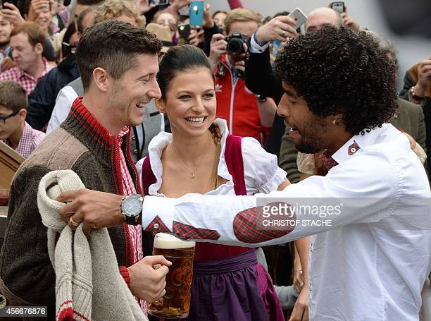 Bayern Munich's Brazilian defender Dante jokes with Bayern Munich's Polish striker Robert Lewandowski and Lewandowski's wife Anna Stachurska as they...