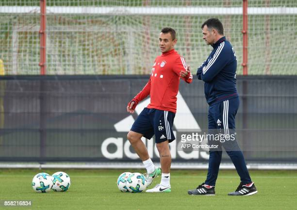 Bayern Munich's Brazilian defender Rafinha and Bayern Munich's French interim coach Willy Sagnol speak together during a training session at the club...