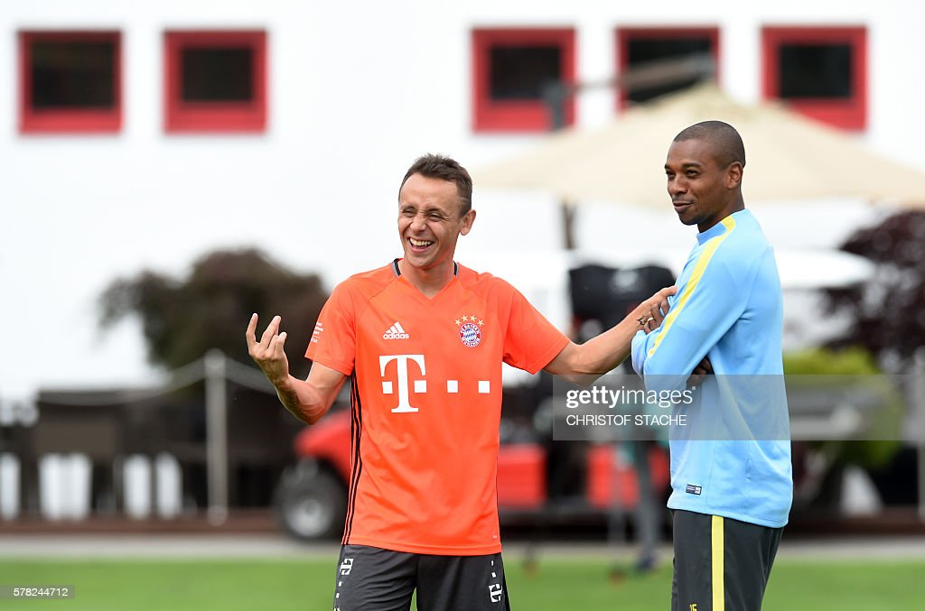 Bayern Munich's Brazilian defender Rafinha (L) jokes with Manchester's Brazilian midfielder Fernandinho Roza (R) after a training of Bayern Munich and ahead a training session of Manchester City at the training ground of the German first division football team FC Bayern Munich in Munich, southern Germany, on July 21, 2016. / AFP / CHRISTOF