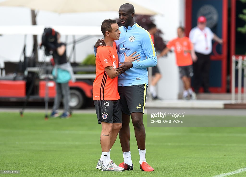 Bayern Munich's Brazilian defender Rafinha (L) Manchester's Ivorian Yaya Toure (R) after a training of Bayern Munich and ahead a training session of Manchester City at the training ground of the German first division football team FC Bayern Munich in Munich, southern Germany, on July 21, 2016. / AFP / CHRISTOF