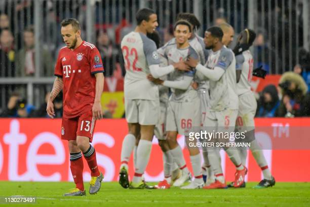 Bayern Munich's Brazilian defender Rafinha reacts as Liverpool's players celebrates scoring the 13 goal during the UEFA Champions League last 16...