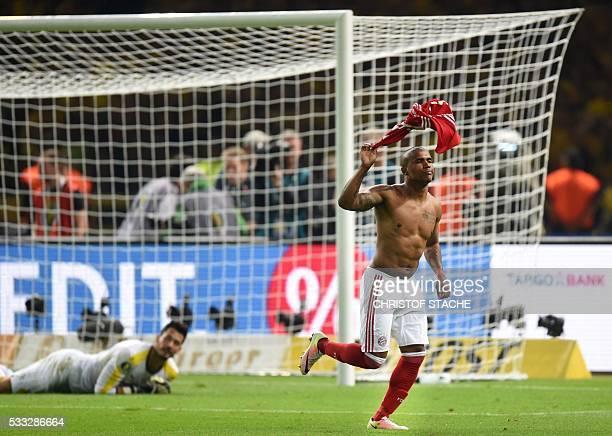 Bayern Munich's Brazilian midfielder Douglas Costa celebrates after scoring he winning goal in the penalty shootout of the German Cup final football...