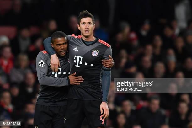 Bayern Munich's Brazilian midfielder Douglas Costa celebrates scoring their third goal with Bayern Munich's Polish forward Robert Lewandowski during...