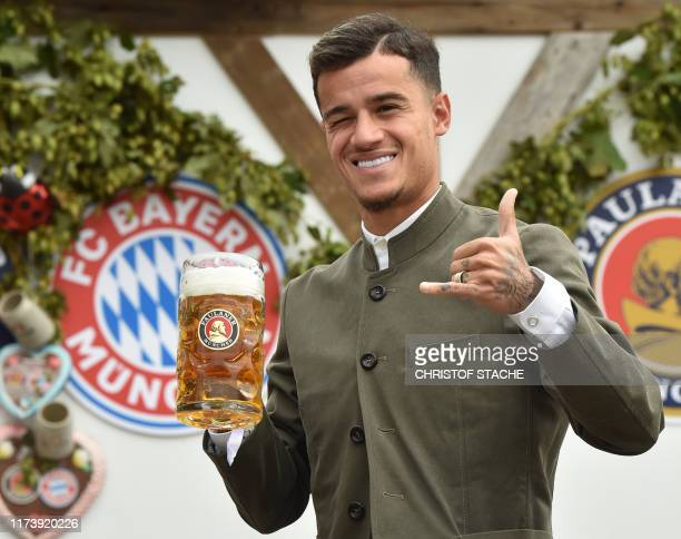 Bayern Munich's Brazilian midfielder Philippe Coutinho wears a traditional Bavarian dress as he poses during his football club's annual visit at the...