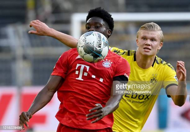 Bayern Munich's Canadian midfielder Alphonso Davies and Dortmund's Norwegian forward Erling Braut Haaland vie for the ball during the German first...