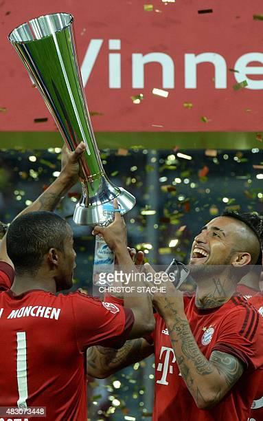 Bayern Munich's Chilean midfielder Arturo Vidal and Bayern Munich's Brazilian midfielder Douglas Costa celebrate after the Audi Cup final football...