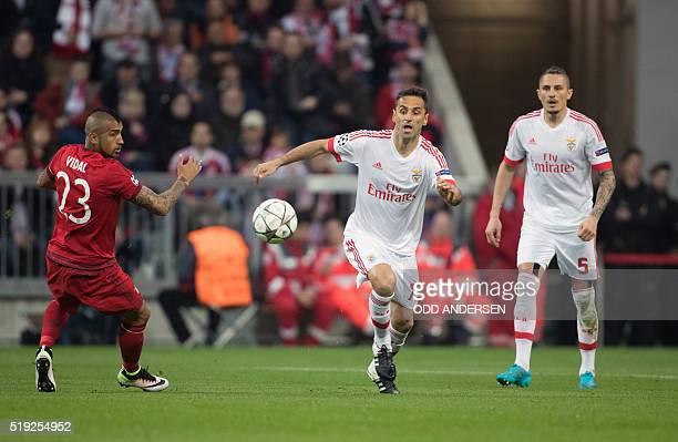 Bayern Munich's Chilean midfielder Arturo Vidal and Benfica's Brazilian forward Jonas vie for the ball during the Champions League quarterfinal...