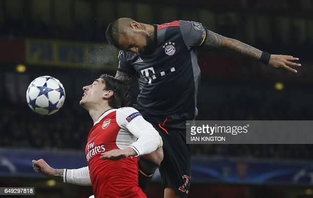 TOPSHOT Bayern Munich's Chilean midfielder Arturo Vidal heads the ball goalward past Arsenal's Spanish defender Hector Bellerin during the UEFA...