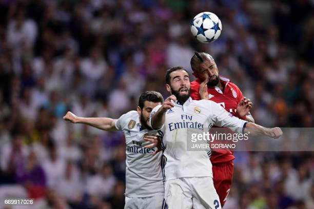Bayern Munich's Chilean midfielder Arturo Vidal jumps for the ball with Real Madrid's defender Dani Carvajal and Real Madrid's defender Nacho...