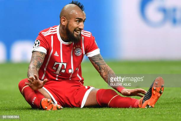 Bayern Munich's Chilean midfielder Arturo Vidal reacts after a challenge during the second leg of the last 16 UEFA Champions League football match...