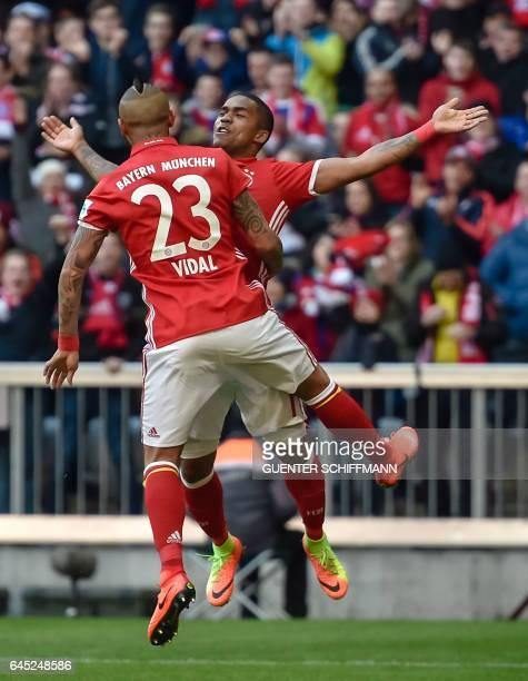 Bayern Munich's Chilian midfielder Arturo Vidal and Bayern Munich's Brazilian midfielder Douglas Costa celebrate the first goal during the German...