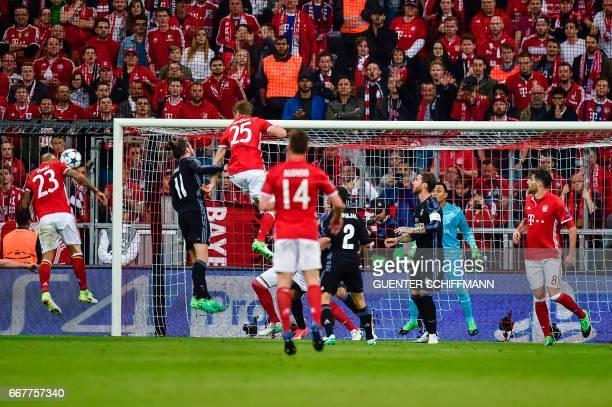 Bayern Munich's Chilian midfielder Arturo Vidal scores the first goal during the UEFA Champions League 1st leg quarterfinal football match FC Bayern...