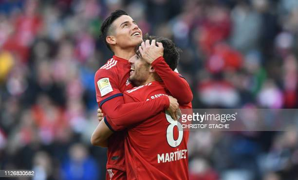 TOPSHOT Bayern Munich's Colombian James Rodriguez congratulates Spanish midfielder Javi Martinez after he scored during the German first division...