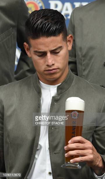 Bayern Munich's Colombian midfielder James Rodriguez is dressed in traditional Bavarian clothes and watches his beer glass during a promotional photo...