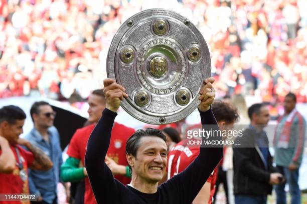 Bayern Munich's Croatian headcoach Niko Kovac celebrates with the trophy after his team's championship victory after the German First division...