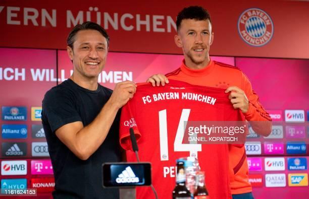 Bayern Munich's Croatian headcoach Niko Kovac poses with the football club's new recruit, Croatian midfielder Ivan Perisic, at Bayern Munich's...