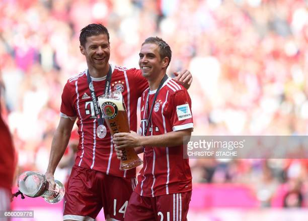 TOPSHOT Bayern Munich's defender Philipp Lahm and Bayern Munich's Spanish midfielder Xabi Alonso celebrate with beer after the German First division...