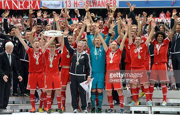 Bayern Munich's defender Philipp Lahm holds the German football league champion's trophy next to head coach Jupp Heynckes while celebrating with...