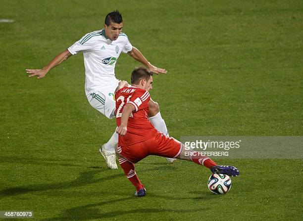 Bayern Munich's defender Philipp Lahm is defended by Morocco Raja Casablanca's Adil Karrouchy during their 2013 FIFA Club World Cup final football...