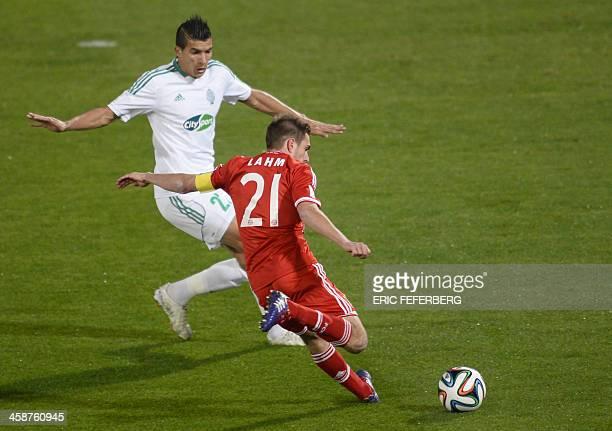 Bayern Munich's defender Philipp Lahm kicks the ball next to Morocco Raja Casablanca's defender Adil Karrouchy during their 2013 FIFA Club World Cup...