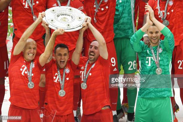 Bayern Munich's Dutch midfielder Arjen Robben Bayern Munich's Brazilian defender Rafinha and Bayern Munich's French midfielder Franck Ribery lift the...