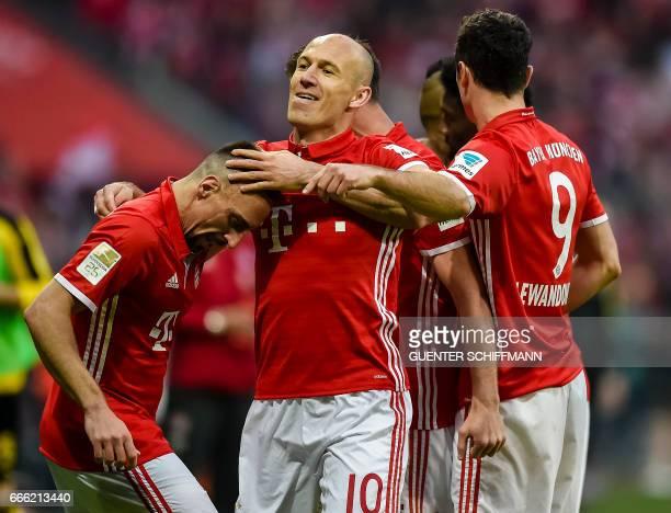 Bayern Munich's Dutch midfielder Arjen Robben celebrates scoring with his teammates during the German first division Bundesliga football match FC...