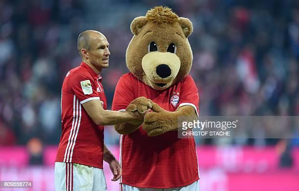 Bayern Munich's Dutch midfielder Arjen Robben greets their mascot after during the German first division Bundesliga football match between FC Bayern...