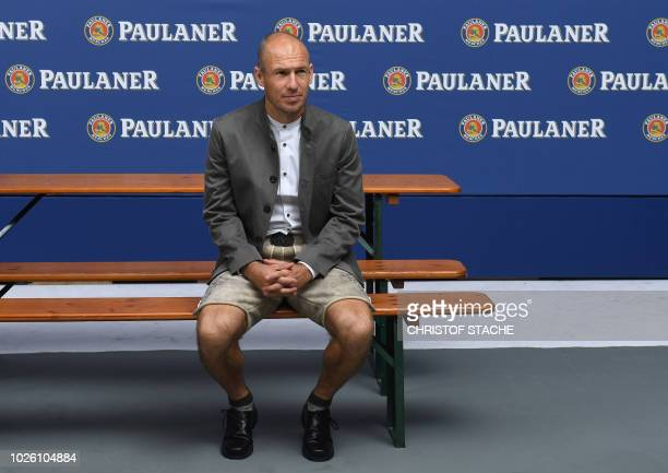 Bayern Munich's Dutch midfielder Arjen Robben is dressed in Bavarian clothes as he sits on a beer bench during a promotional photo shooting event in...