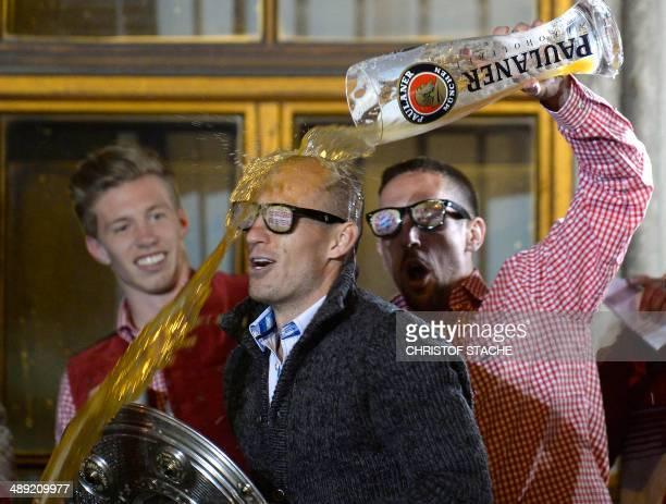 Bayern Munich's Dutch midfielder Arjen Robben is sprayed with beer by Bayern Munich's French midfielder Franck Ribery on Munich's city hall balcony...