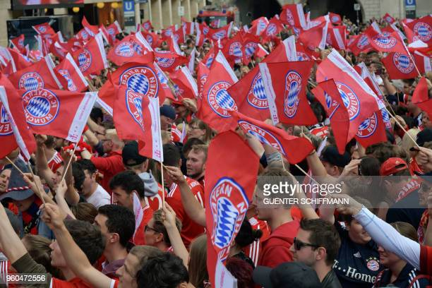 Bayern Munich's fans wave flags as players celebrate on the balcony of the city hall in Munich southern Germany on May 20 2018