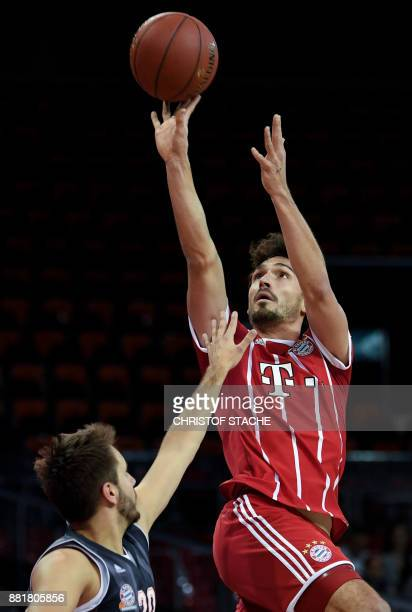Bayern Munich's football defender Mats Hummels shoots the ball during a basketball match at a sponsor fan event in Munich southern Germany on...