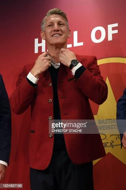 Bayern Munich's former midfielder Bastian Schweinsteiger wears the socalled legend's jacket in the Hall of fame in the Bayern Munich team's museum...