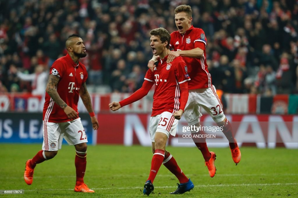Bayern Munich's forward Thomas Mueller (C) celebrate scoring the 5-1 goal with his teammates during the UEFA Champions League round of sixteen football match between FC Bayern Munich and Arsenal in Munich, southern Germany, on February 15, 2017. / AFP / Odd ANDERSEN