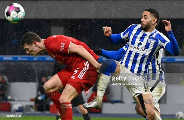 Bayern Munich's French defender Benjamin Pavard and Hertha Berlin's Brazilian forward Matheus Cunha vie for the ball during the German first division...