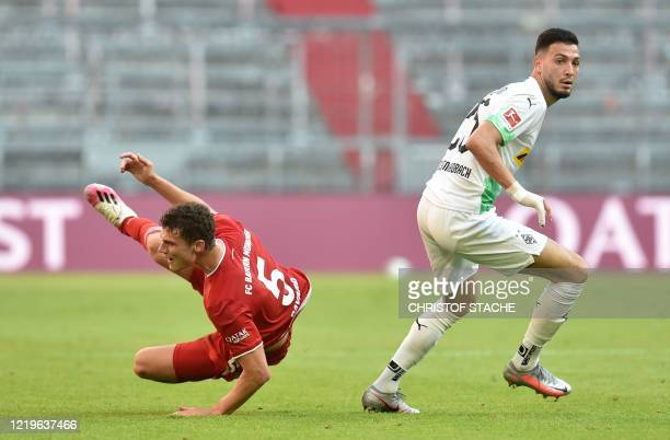 Bayern Munich's French defender Benjamin Pavard and Moenchengladbach's Algerian defender Ramy Bensebaini vie for the ball during the German first...