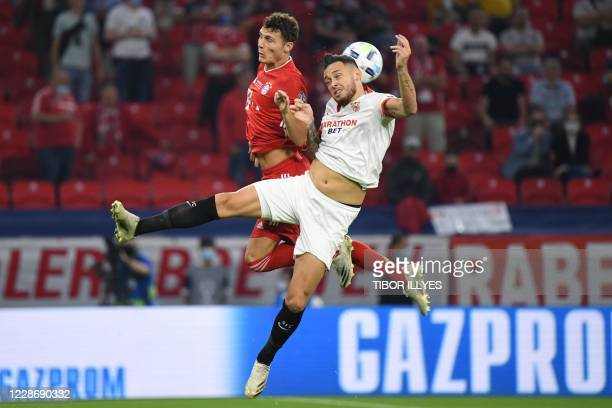 Bayern Munich's French defender Benjamin Pavard jumps for the ball with Sevilla's Argentinian midfielder Lucas Ocampos during the UEFA Super Cup...