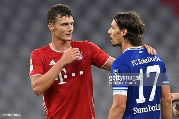 Bayern Munich's French defender Benjamin Pavard speaks with Schalke's French midfielder Benjamin Stambouli after the German first division Bundesliga...