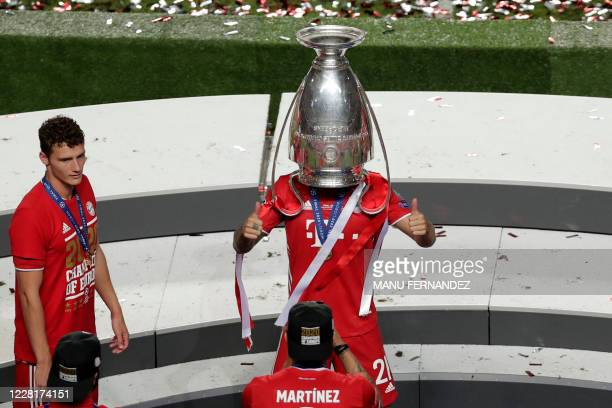 Bayern Munich's French defender Lucas Hernandez poses with the trophy upside down on his head next to Bayern Munich's French defender Benjamin Pavard...