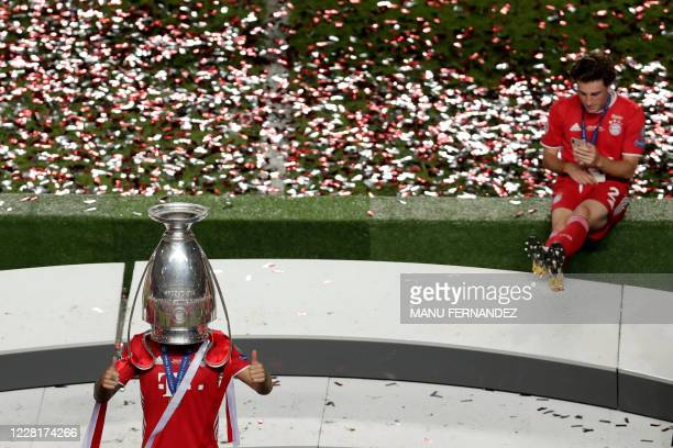 Bayern Munich's French defender Lucas Hernandez poses with the trophy upside down on his head as he celebrates after Bayern won the UEFA Champions...