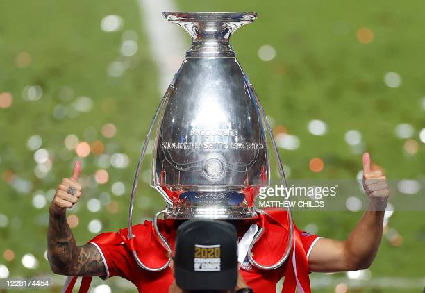 Bayern Munich's French defender Lucas Hernandez poses with the trophy upside down on his head after Bayern won the UEFA Champions League final...