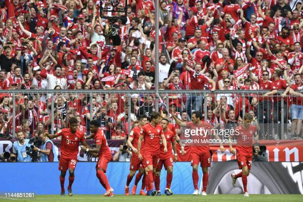 Bayern Munich's French forward Kingsley Coman celebrates scoring the opening goal with his teammates during the German First division Bundesliga...