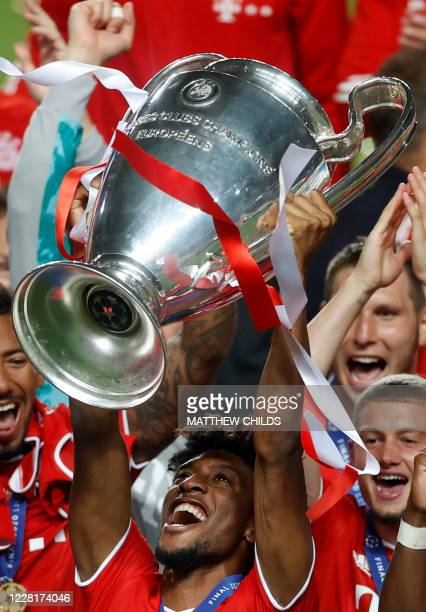 Bayern Munich's French forward Kingsley Coman raises the European Champion Clubs' Cup during the trophy ceremony after winning at the end of the UEFA...